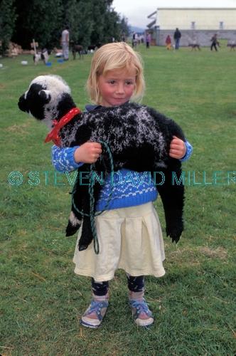 little girl holding pet;little girl holding lamb;school fete;new zealand girl;girl in new zealand.